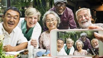 A group of older people smiling and taking selfies.