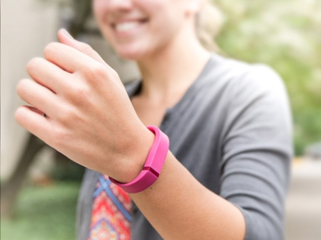 An IQ Solutions employee exercising while using her fitbit device