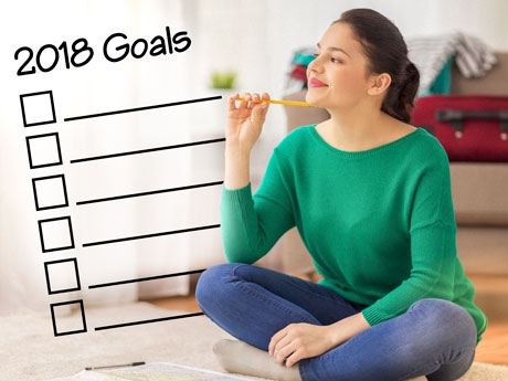 A woman holding a pencil thinking about her goals.