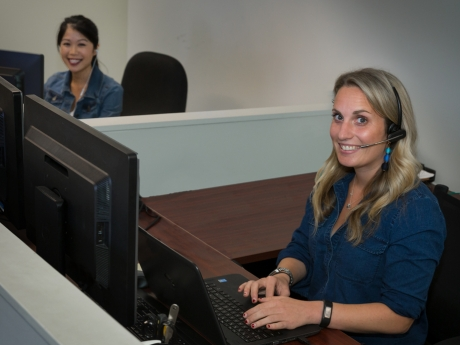 A woman smiling at a computer using a headset.